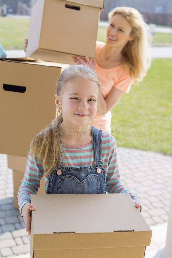 Moeder en dochter met kartondozen die zich in nieuw huis bewegen stock foto's