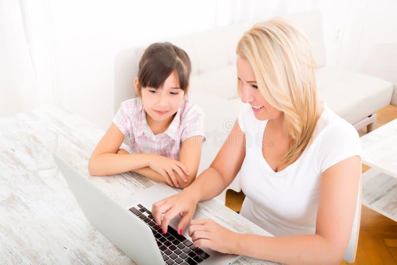 Moeder en Dochter met Laptop thuis royalty-vrije stock fotografie