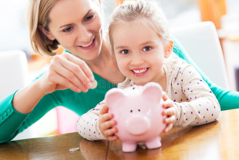 Moeder en dochter met spaarvarken royalty-vrije stock afbeelding