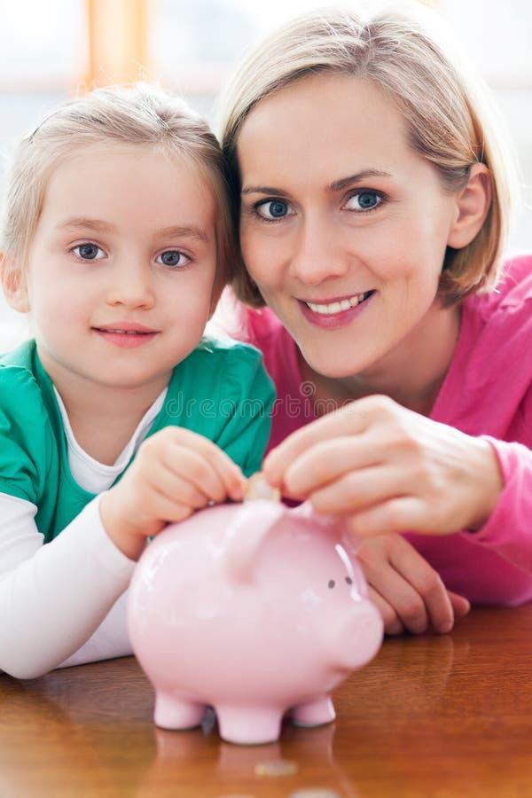 Moeder en dochter met spaarvarken stock foto's