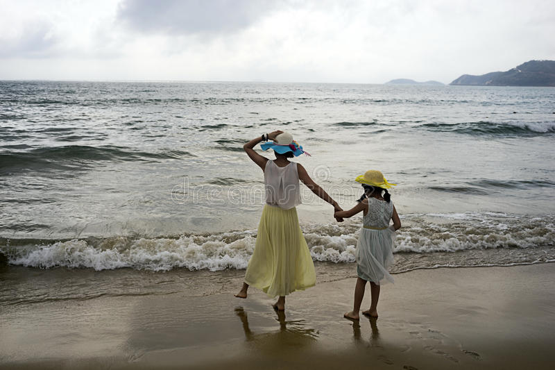 Moeder en dochter op de overzeese kust stock foto's