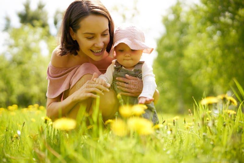 Moeder en dochter op een weide met paardebloemen stock afbeeldingen