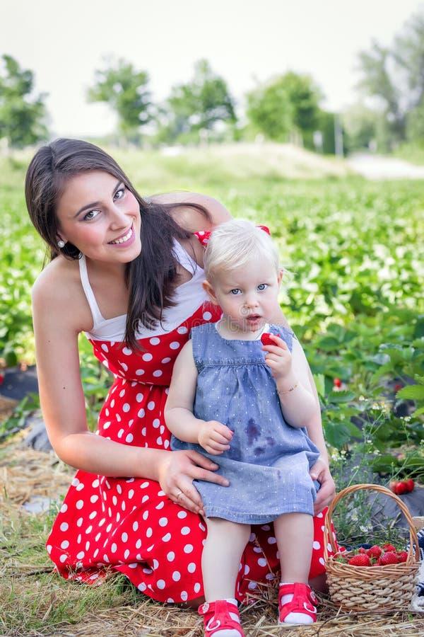 Moeder en dochter op het aardbeigebied royalty-vrije stock afbeeldingen
