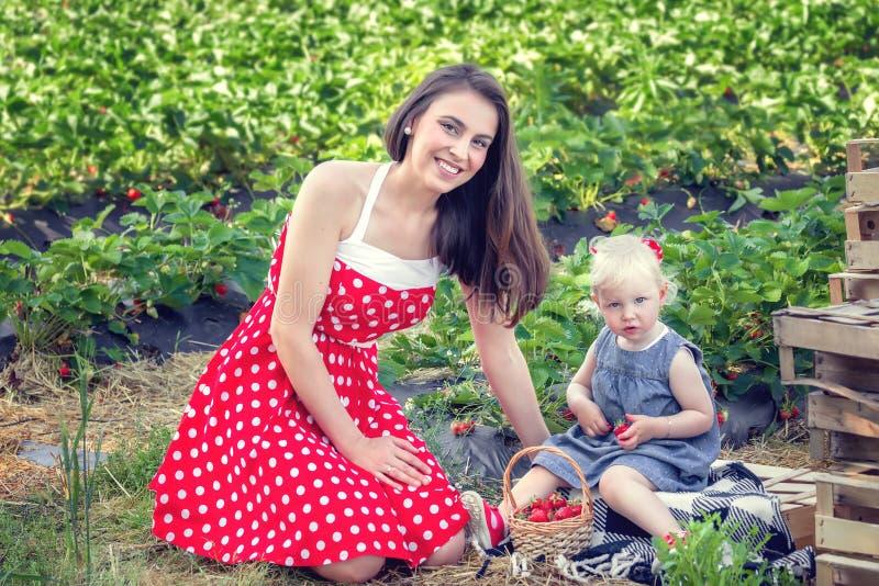 Moeder en dochter op het aardbeigebied stock fotografie