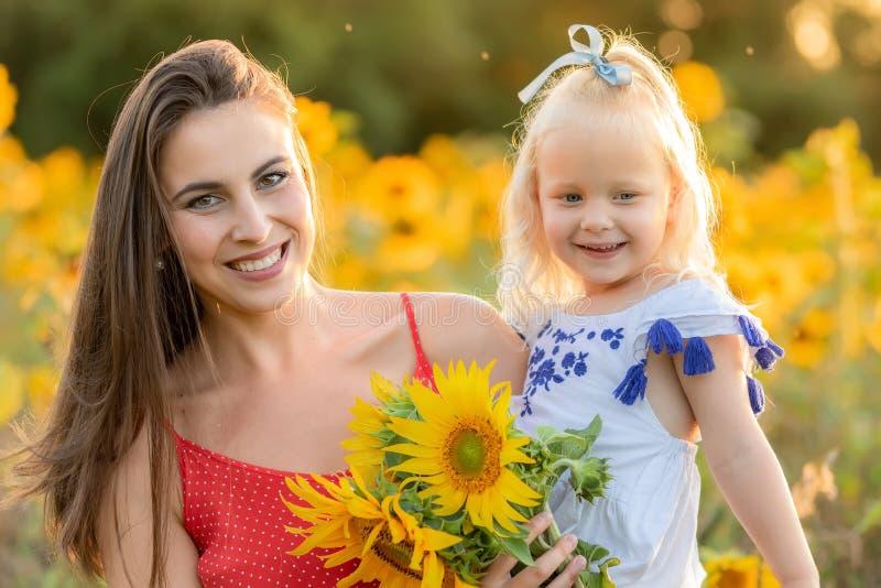 Moeder en dochter op het gebied met zonnebloemen stock foto's