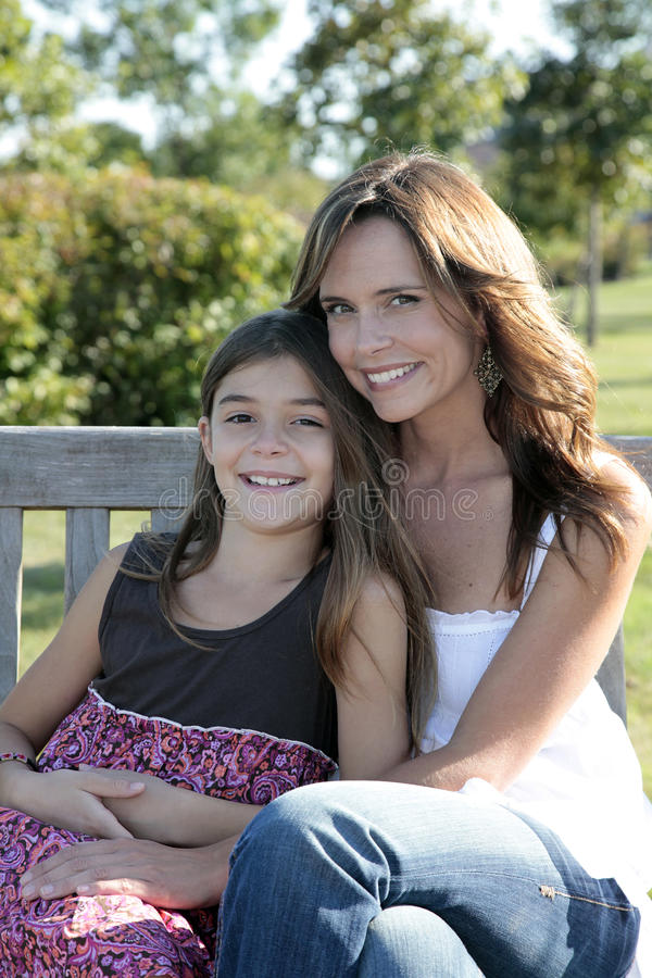 Moeder en dochter op parkbank stock foto