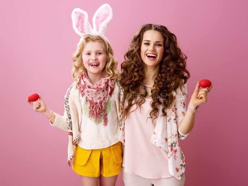 Moeder en dochter op roze achtergrond met rode paaseieren stock afbeelding