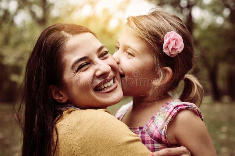 Moeder en dochter in openlucht in een weide Meisje die hij kussen royalty-vrije stock foto