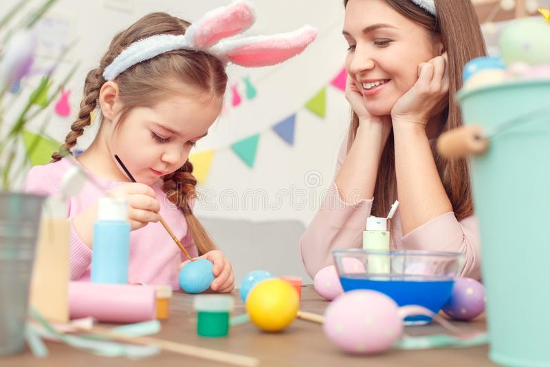 Moeder en dochter samen thuis voorbereiding van Pasen in de geconcentreerde konijntjesoren die meisje het schilderen punten zitte royalty-vrije stock foto