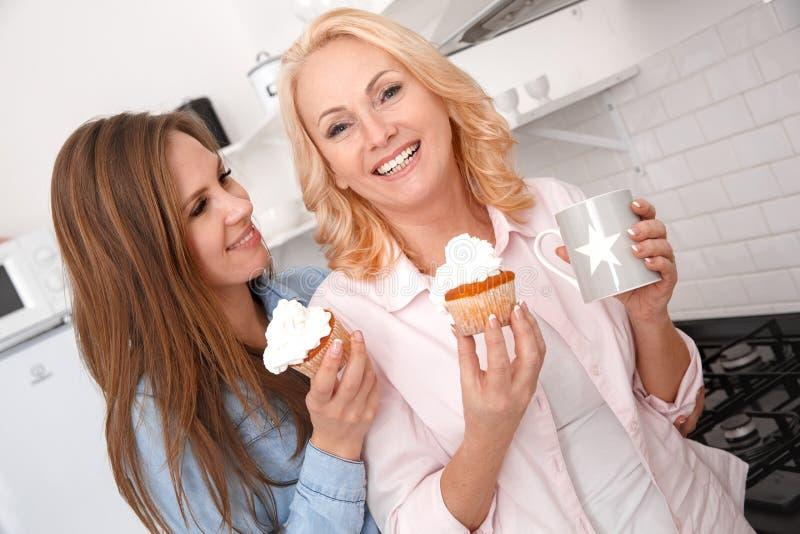 Moeder en dochter samen thuis weekend die cupcakes eten stock afbeelding