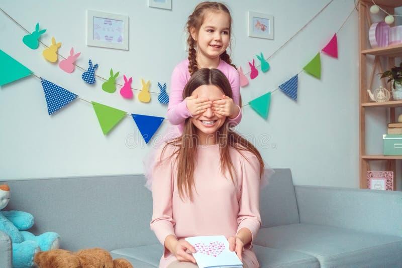 Moeder en dochter samen weekend thuis op bankmeisje die tot verrassing maken aan mamma royalty-vrije stock foto