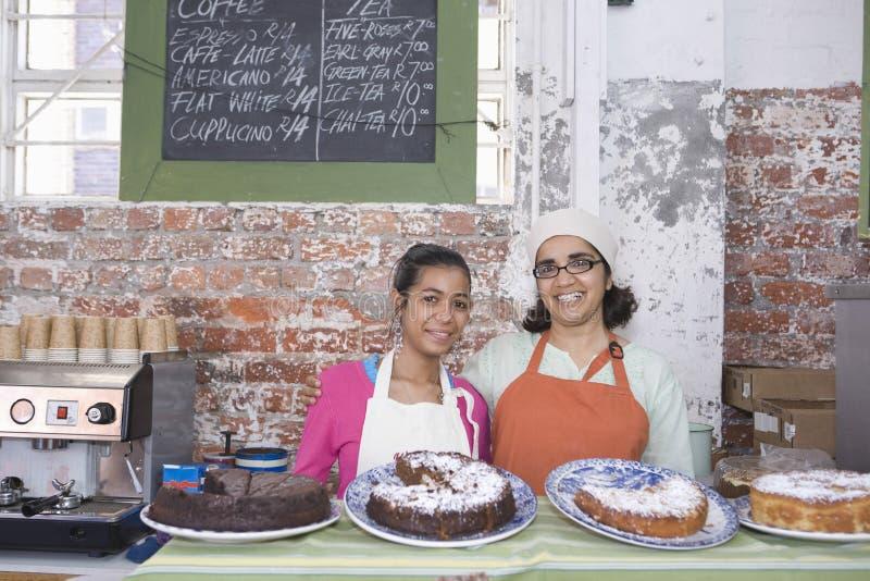Moeder en Dochter in Schorten die zich bij de Teller van de Cakewinkel bevinden stock afbeeldingen
