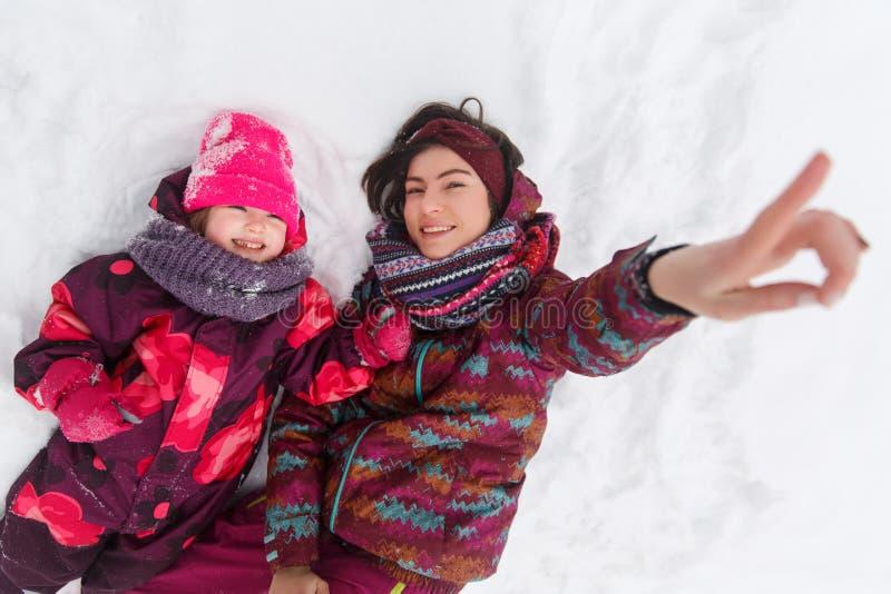 Moeder en dochter in sneeuw royalty-vrije stock afbeelding