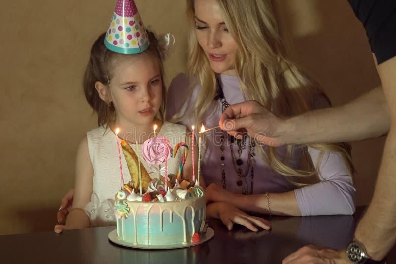Moeder en dochter tellende kaarsen op een verjaardagscake meisje in een feestelijke hoed bij een children& x27; s partij stock foto