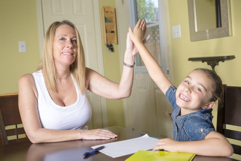 Moeder en Dochter thuis Het meisjethuiswerk van het mamma teachs stock foto