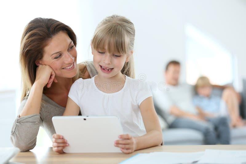 Moeder en dochter usng tablet stock fotografie
