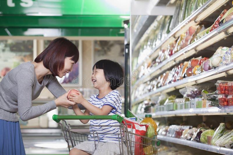 Moeder en dochterholdingsappel, die voor kruidenierswinkels, Peking winkelen stock foto