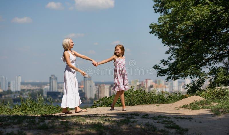 Moeder en dochterholdingshanden, die in stadspark lopen royalty-vrije stock foto