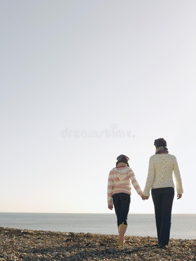 Moeder en dochterholdingshanden en het Lopen op Strand stock foto's