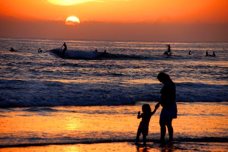 Moeder en dochterholdingshanden op het strand in de zonsondergang royalty-vrije stock foto's