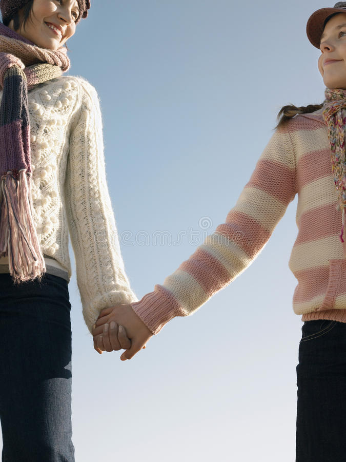 Moeder en Dochterholdingshanden tegen Hemel royalty-vrije stock foto