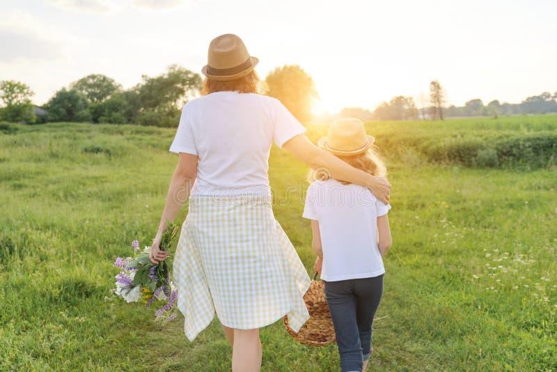 Moeder en dochterkind die langs de weide, mening van de rug lopen royalty-vrije stock foto