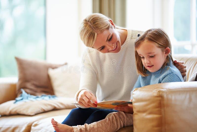 Moeder en Dochterlezingsverhaal thuis samen royalty-vrije stock afbeeldingen