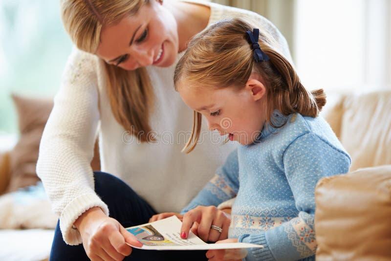 Moeder en Dochterlezingsverhaal thuis samen stock afbeeldingen