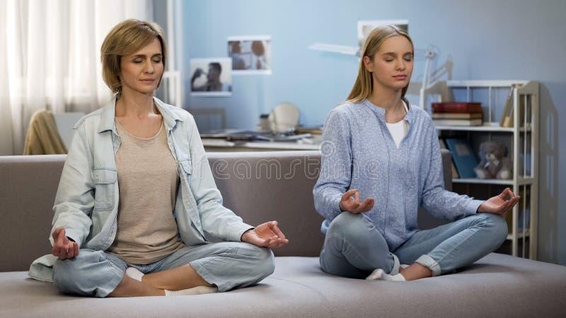 Moeder en dochtermeditatie thuis, yogapraktijk, wederzijds begrip stock foto's