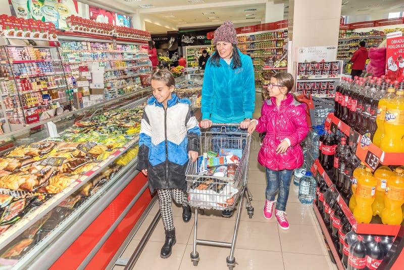 Moeder en dochters die in kruidenierswinkelopslag winkelen stock afbeeldingen