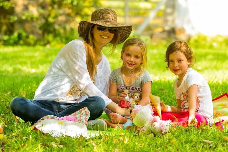 Moeder en dochters die op een picknickdeken bij de Winter S zitten royalty-vrije stock foto