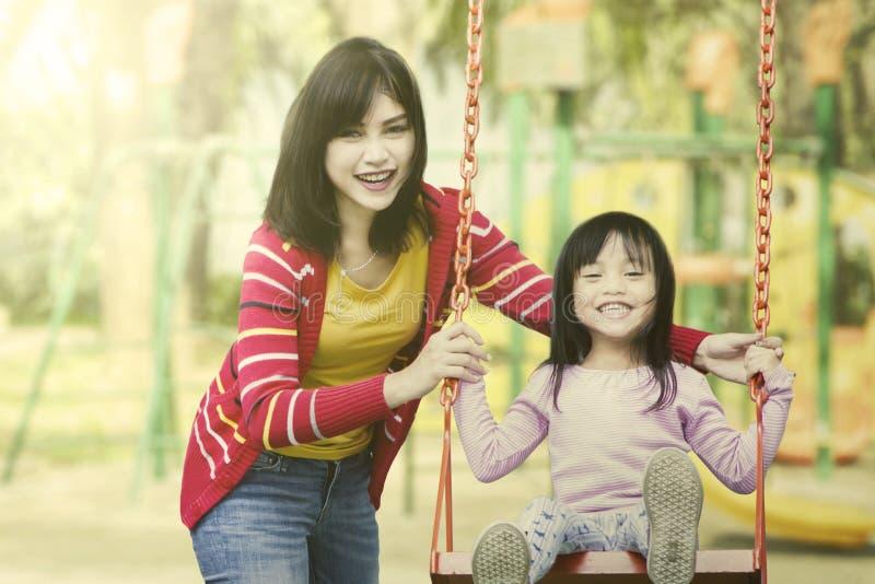 Moeder en dochterspel samen bij speelplaats stock fotografie