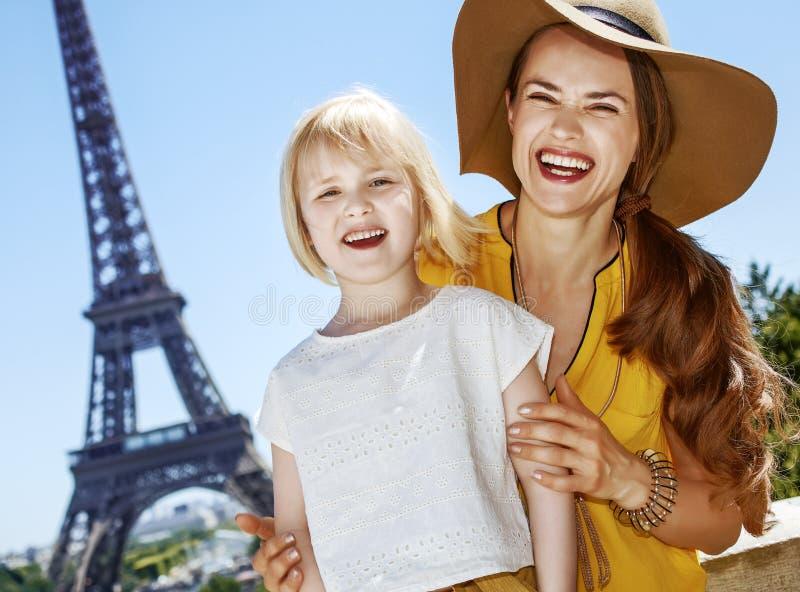 Moeder en dochtertoeristen die zich voor de toren van Eiffel bevinden royalty-vrije stock afbeelding