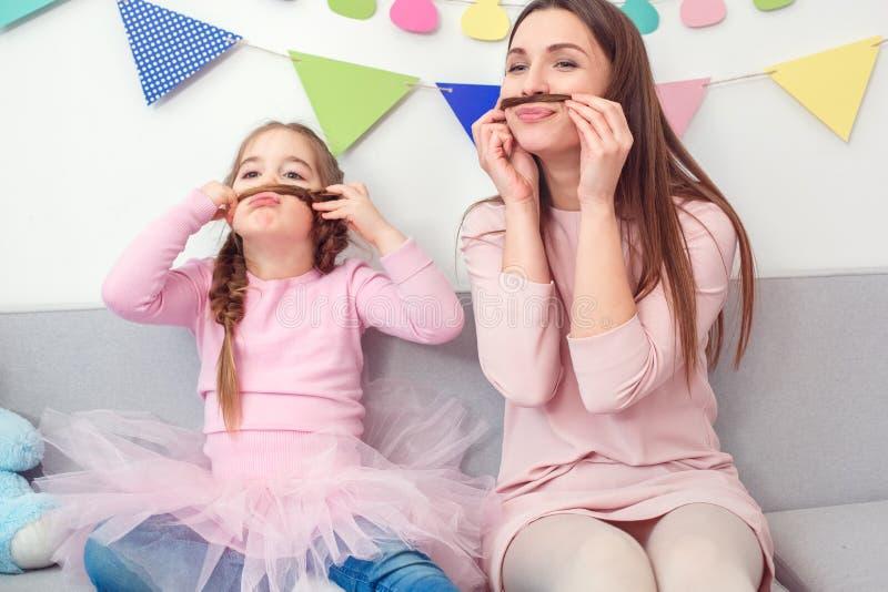 Moeder en dochterweekend die samen thuis grimas zitten royalty-vrije stock foto's