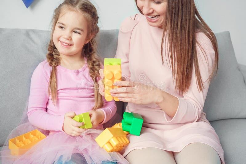 Moeder en dochterweekend die samen thuis met stuk speelgoed bakstenen spelen royalty-vrije stock foto's