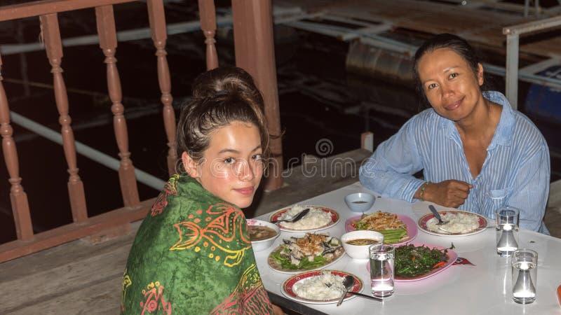 Moeder en dochterzitting bij lijst het eten royalty-vrije stock foto