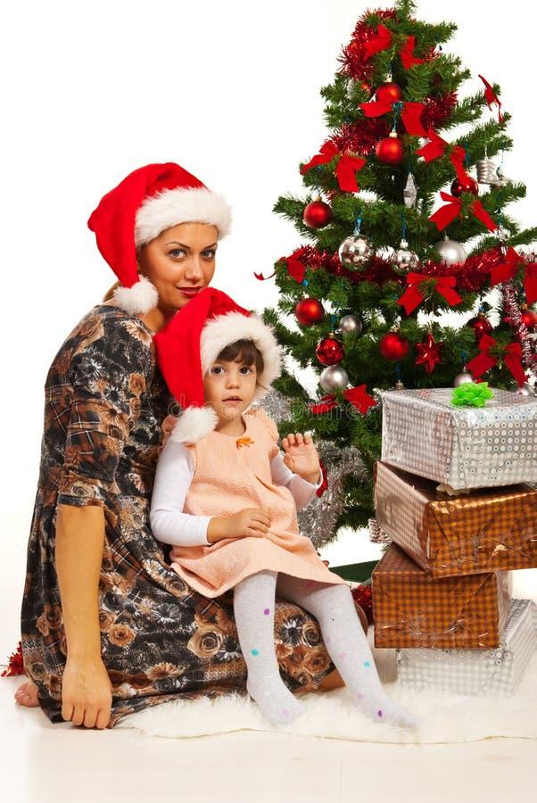 Moeder en dochterzitting dichtbij Kerstmisboom stock foto's