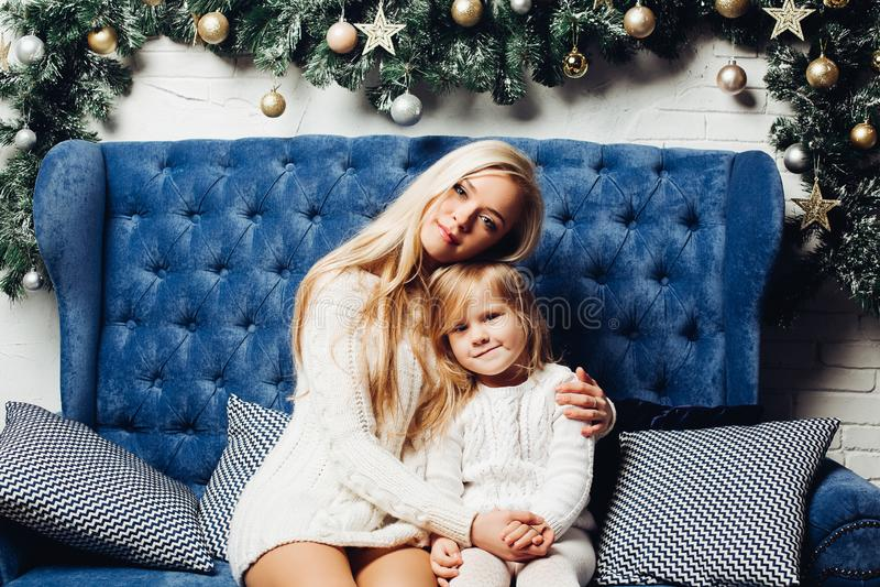 Moeder en dochterzitting en het koesteren dichtbij Kerstmisboom royalty-vrije stock afbeelding