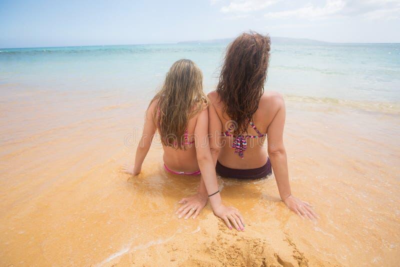 Moeder en dochterzitting op een zandig strand stock afbeelding