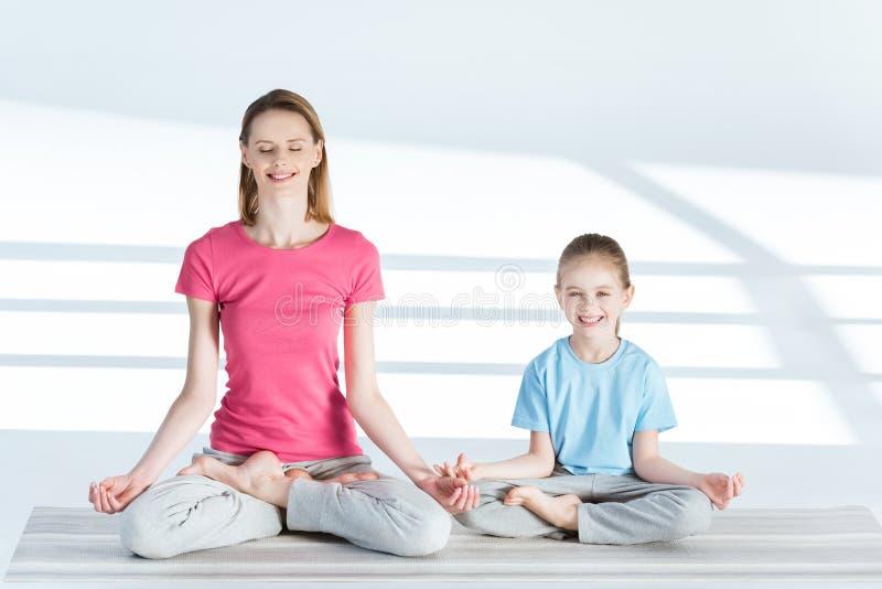 Moeder en dochterzitting op yogamat in lotusbloempositie en het glimlachen bij camera royalty-vrije stock afbeelding