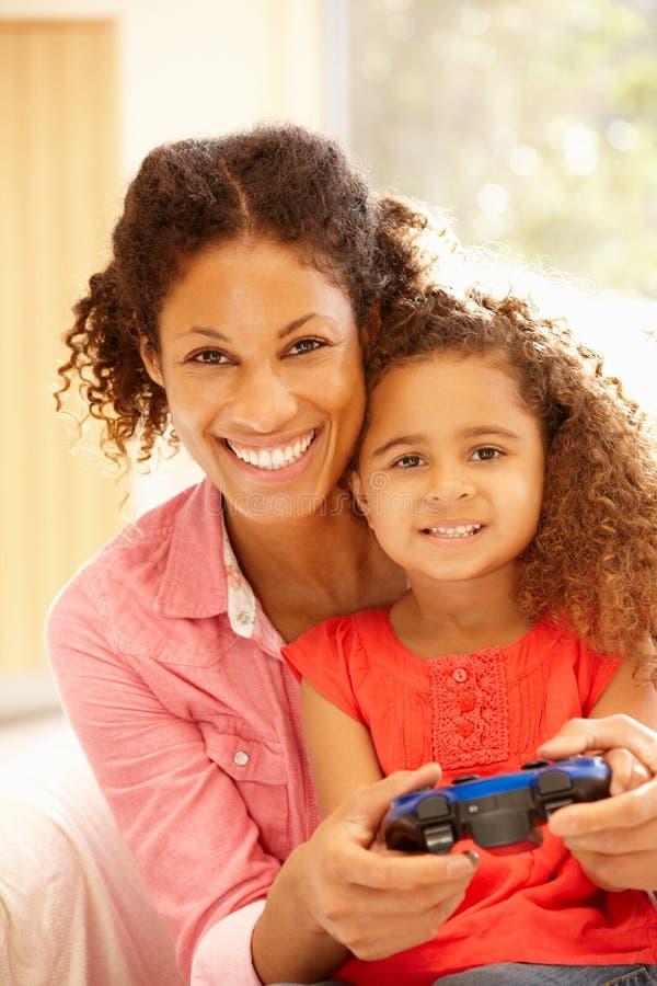 Moeder en duaghter speelcomputerspelen stock afbeeldingen