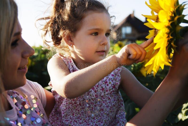 Moeder en een dochter in de zonnebloemen royalty-vrije stock afbeeldingen