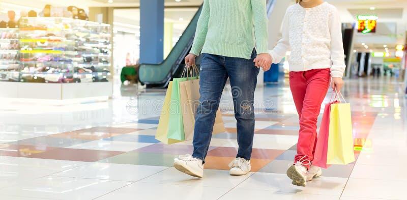 Moeder en een kind die met het winkelen zakken in de wandelgalerij lopen stock afbeelding