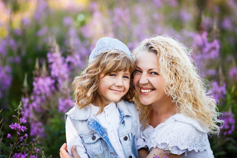 Moeder en een leuke kleine zoon die en pret in fild met bloemen in de zomer koesteren hebben Familie en gelukconcept royalty-vrije stock fotografie