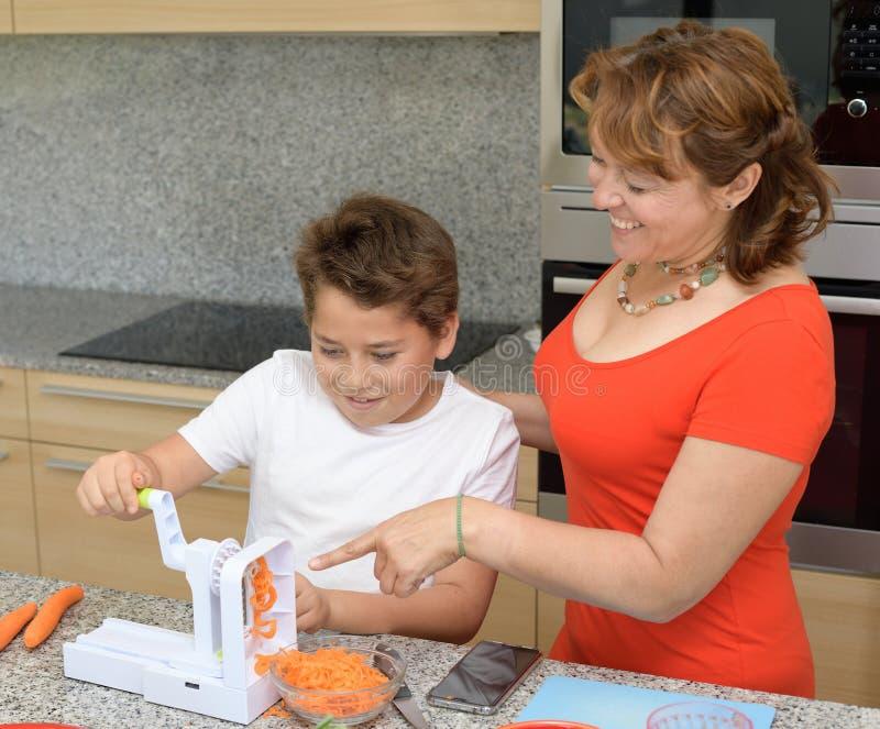 Moeder en een zeer geinteresseerde zoon die lunch in de gelukkige keuken voorbereiden royalty-vrije stock afbeelding