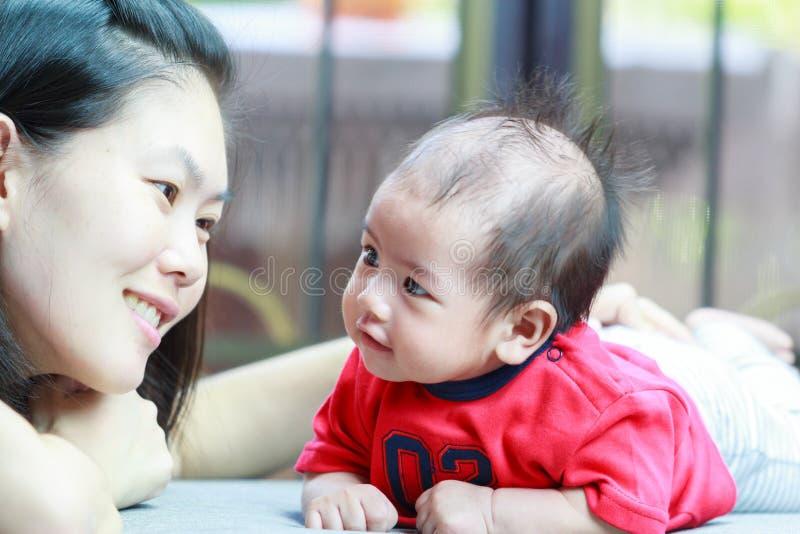 Moeder en haar baby die aan elkaar kijken stock foto's