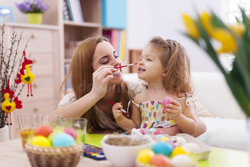 Moeder en haar baby die paaseieren schilderen stock afbeeldingen