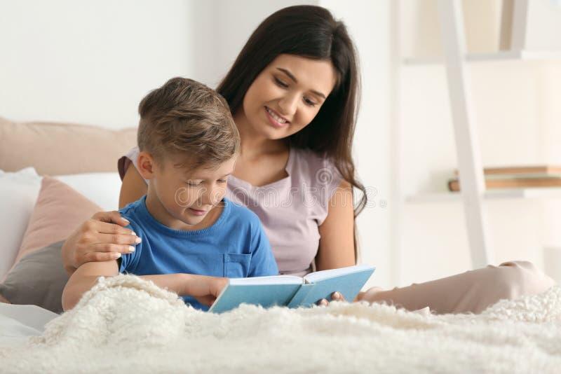 Moeder en haar boek van de zoonslezing samen thuis royalty-vrije stock afbeeldingen