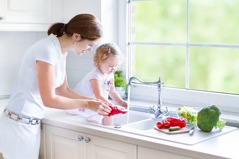 Moeder en haar de wasgroenten van de peuterdochter stock afbeeldingen