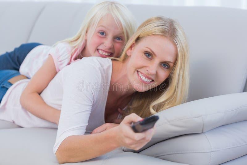 Moeder en haar dochter die op TV letten royalty-vrije stock foto's